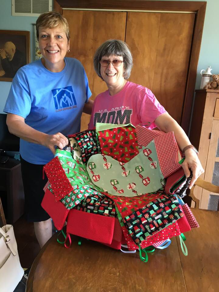 Kim Jackson and Karen Wingate hold a basket of the Christmas Stockings of Joy